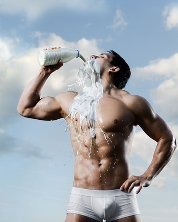 athletic type: the very muscular handsome sexy guy on sky background, drink milk Stock Photo
