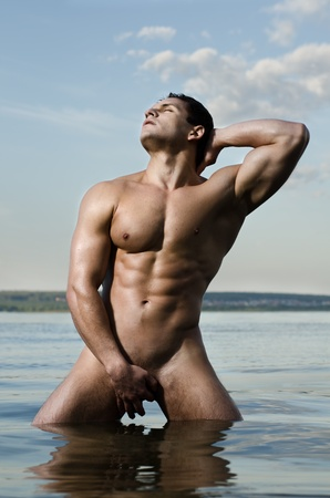 the very muscular handsome sexy guy on sky and sea background photo