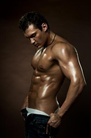 hombre flaco: el chico guapo sexy muy muscular en el fondo de color marr�n oscuro, estricta Foto de archivo