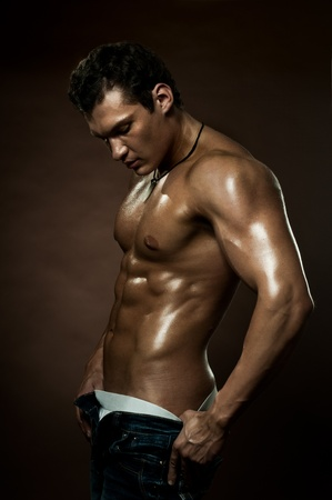 the very muscular handsome sexy guy on dark  brown background, strict