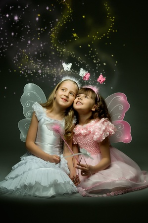 gleam: two beautiful  little girl with wings, sit and  smile on dark background
