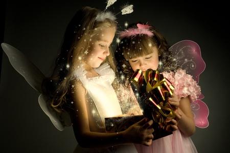splendour: two little girl examine gift in fancy box, smile, on dark background