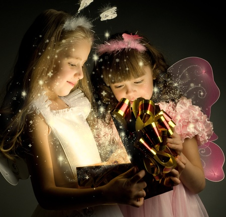 christmas girl: two little girl examine gift in fancy box, smile, on dark background