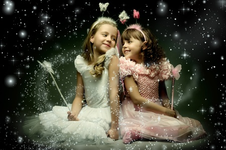 girl magic wand: two beautiful  little girl with wings, sit and  smile on dark starry sky background