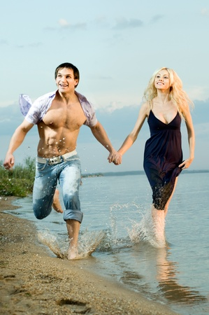 sexy beauty guy and girl outdoor in river, fast run on beach and happy smile Stock Photo - 11219874