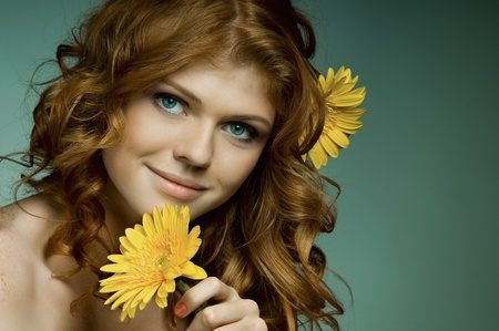 the very  pretty red-haired freckled young woman with yelow flowers , horizontal portrait photo