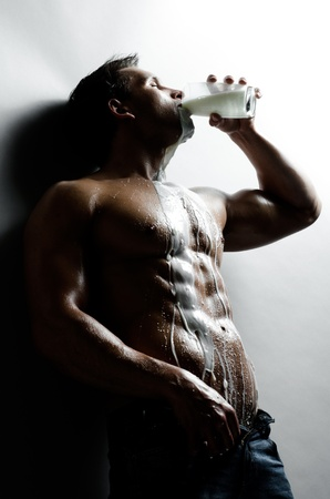 the very sexy muscular handsome sexy guy , drink milk and pour on body
