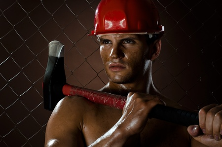 erector:  the beauty muscular worker  chopper  man, in  safety helmet  with big  heavy ax  in hands, on netting fence background