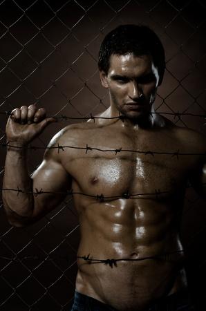 preso: el chico guapo delincuente muy musculoso, de redes de cerco de acero