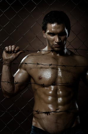 prisoner man: the very muscular handsome felon guy ,  out of netting   steel fence Stock Photo