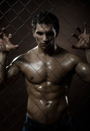 miscreant: the very muscular handsome felon guy ,  out of netting   steel fence Stock Photo