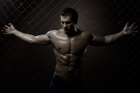 courageous: the very muscular handsome sexy guy ,  on  netting   steel fence Stock Photo