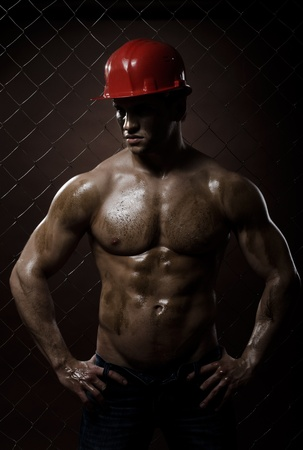 the beauty muscular worker  man, in  safety helmet , on netting fence background Stock Photo - 11385887