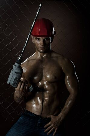 driller:  the beauty muscular worker driller man ,  hold  big perforator in hand, vertical photo Stock Photo
