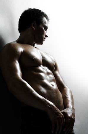 hombre flaco: el chico guapo sexy muy muscular en el fondo de la pared gris