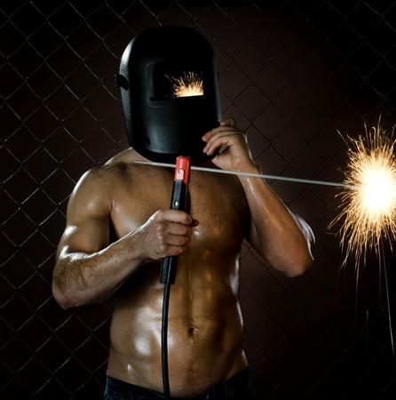 fabrication:  the beauty muscular worker welder  man, weld  electric arc-weld, on netting fence background