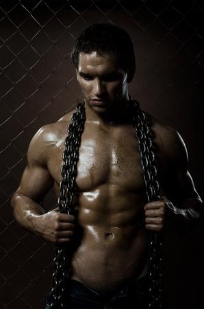 sudoroso: el hombre la belleza trabajador musculoso, con la cadena en las manos, sobre la compensaci�n de fondo cerca de
