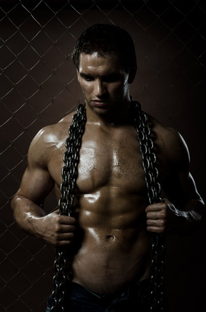 sweaty:  the beauty muscular worker  man,  with  chain in hands, on netting fence background Stock Photo