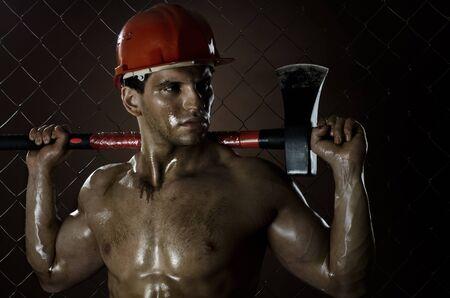 safety helmet: la belleza trabajador musculoso hombre helic�ptero, en el casco de seguridad con gran hacha pesada en las manos, aspecto cansado, en el fondo cerca de malla