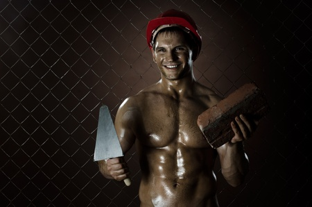 muscularity:  the beauty muscular worker  man, in  safety helmet  with trowel and brick  in hands and smile, on netting fence background