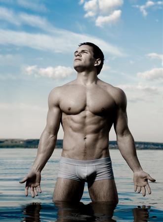 bloke: il bel ragazzo muscoloso, sexy sul cielo e lo sfondo del mare