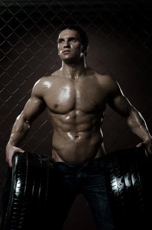netting: de zeer gespierde knappe sexy man met rubberen band, betreffende de saldering stalen hek achtergrond