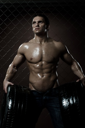 courageous: the very muscular handsome sexy guy with rubber-tire,  on  netting  steel fence background Stock Photo