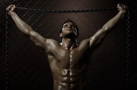 ceppi: il bel ragazzo molto muscoloso stanco sexy, su rete recinzione in acciaio con catena in acciaio Archivio Fotografico