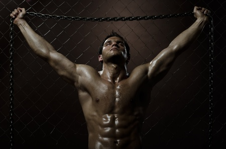 the very muscular handsome weary sexy guy ,  on  netting   steel fence with steel chain photo