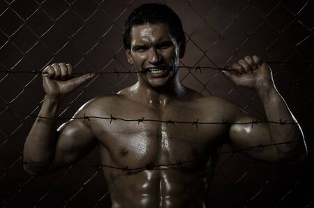 the very muscular handsome felon guy ,  out of netting   steel fence with  barbed wire photo