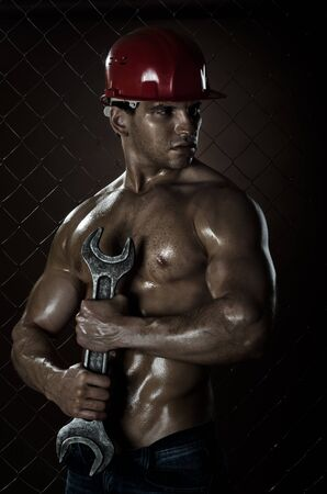 erector:  the beauty muscular worker  man, in  safety helmet  with big wrench  in hands, on netting fence background Stock Photo