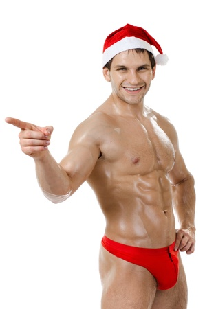 gaily: the very muscular  bronzed handsome sexy Santa Claus on white  background, posture  show  index finger and smile, isolated