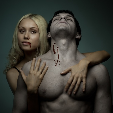 bite: muscular handsome sexy guy with pretty  vampire woman, on dark background, glamour  light
