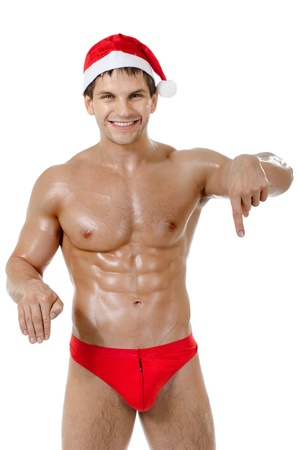 the very muscular  bronzed handsome sexy Santa Claus on white  background, posture  show  index finger and smile, isolated photo