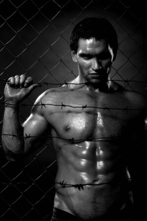 the very muscular handsome felon guy ,  out of netting   steel fence Stock Photo - 11391454