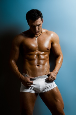 young underwear: the very muscular bronzed handsome sexy guy on  blue background, hard light Stock Photo