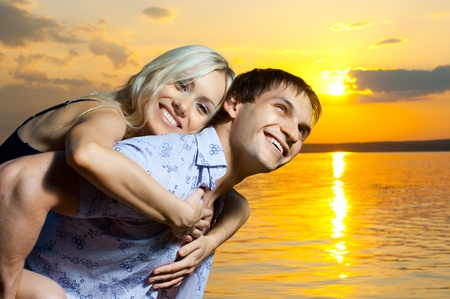 necking: very happy  sexy pretty couple,  smile, outdoor on orange  sunset, horizontal photo