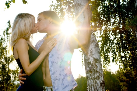 romantic evening date on nature, couple on beautiful sunset kiss photo