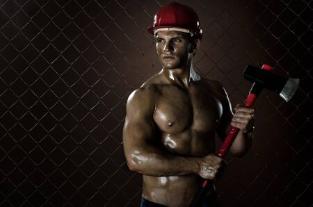 muddy:  the beauty muscular worker  chopper  man, in  safety helmet  with big  heavy ax  in hands, tired  appearance , on netting fence background Stock Photo