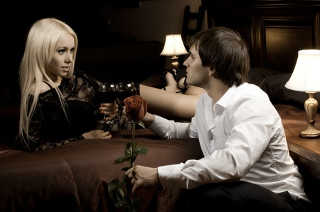 romantic evening date in hotel room, guy with red rose and sexy girl,  on bed photo