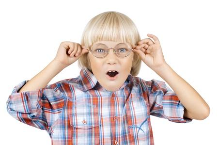 asombro: niño de los niños poco alegres sorprendió la mirada de la cámara por encima de gafas, en el fondo blanco, aislados Foto de archivo