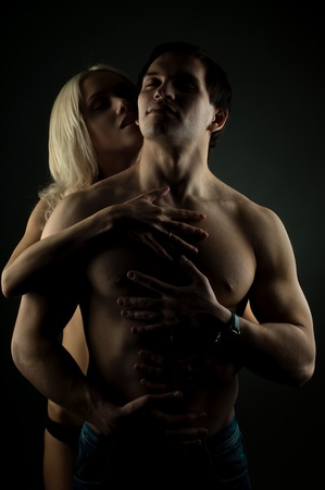 sexy couple: muscular handsome sexy guy with pretty woman, on dark background, glamour  light