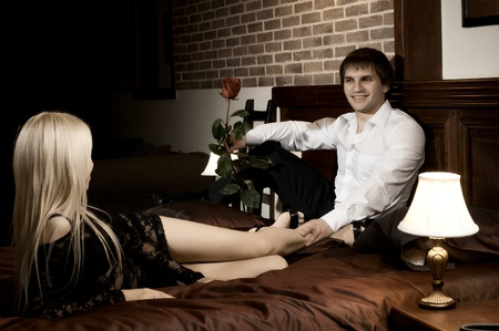 sexy couple in bed: romantic evening date in hotel room, guy with red rose smile,  on bed Stock Photo