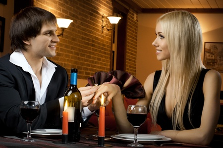 romantic evening date in hotel room, or supper in restaurant, guy make  engagement ring his beautiful woman  photo