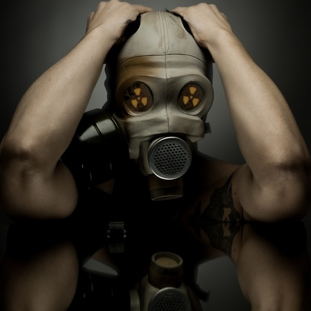 contamination: man in  gas-mask ongray background,   radiation and anti-gas  protection  concept
