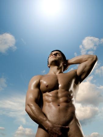männer nackt: die sehr muskulös bronziert schön sexy Kerl auf Himmel Hintergrund, Haltung