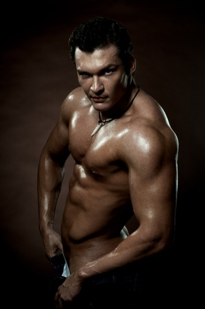 courageous: the very muscular handsome sexy guy on dark  brown background, strict