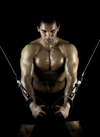 very: very power athletic guy ,  execute exercise on  on sport-apparatus, in  sport-hall, beauty glamour light