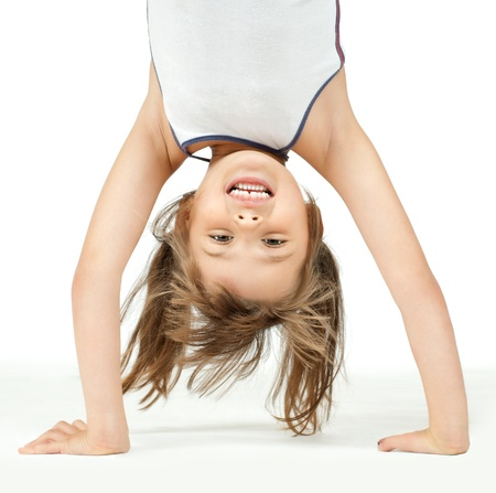 little children girl  stand head over heels and smile, on white background, isolated