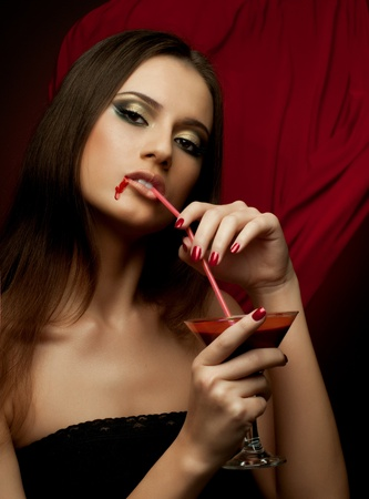 the very  pretty woman vamp, with glass and blood , sensual sexuality gaze photo
